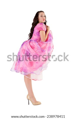 Portrait of attractive sexy girl in pink dress looking up at camera, isolated over white background.   Fashion concept with tall model.