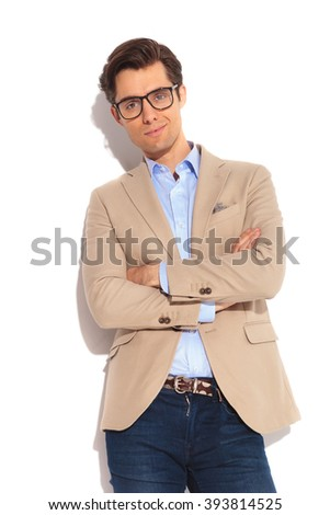 portrait of attractive smart casual man in jeans posing in isolated studio background with hands crossed, looking at the camera - stock photo