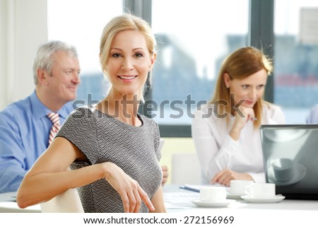 Portrait of attractive smiling businesswoman sitting at meeting while business people sitting at background and working on business report. Teamwork at office. - stock photo