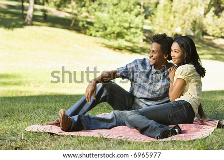 Portrait of attractive smiling couple in park sitting on picnic blanket.