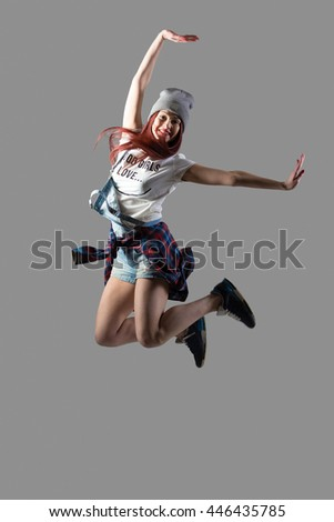 Portrait of attractive smiling fit cute hipster casual young woman wearing beanie dancing and jumping with happy face. Modern style beautiful dancer working out. Full length, studio gray background - stock photo