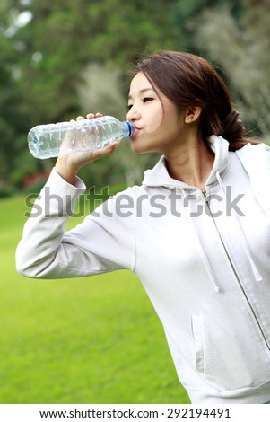 portrait of attractive sporty woman drinking mineral water during break after workout - stock photo
