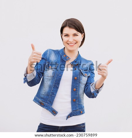 Portrait of attractive teenage girl showing thumbs up gesture. Isolated on gray background  - stock photo