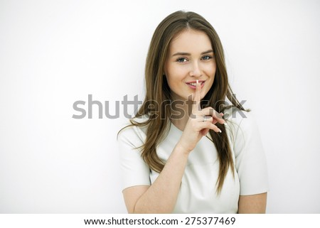 Portrait of attractive teenage girl with finger on lips, isolated over white background concept of student show quiet, silence, secret gesture, young pretty brunette woman - stock photo