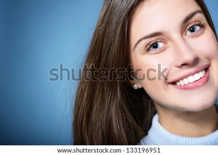 portrait of attractive teenager girl smiling in cheerful mood, over blue - stock photo