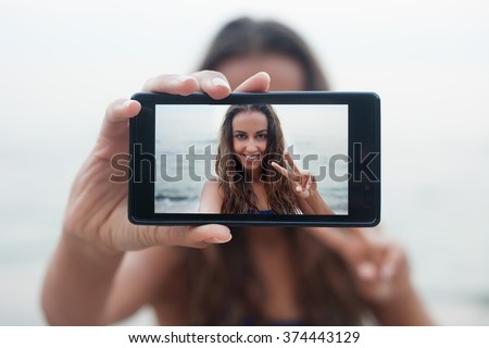 Portrait of attractive teenager girl standing on a summer sandy beach on holiday, holding a smartphone device taking selfies pictures of herself on vacation against blue sky. People travel technology. - stock photo