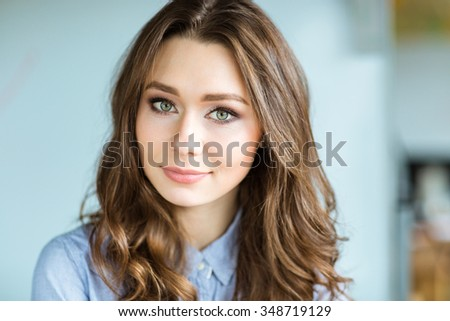 Portrait of attractive thoughtful young curly woman looking at camera - stock photo