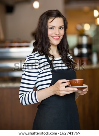 Portrait of attractive waitress holding coffee cup while standing in cafeteria