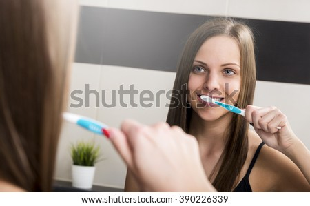 Portrait of attractive woman brushing teeth in bathroom - stock photo