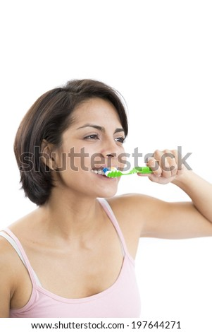 Portrait Of Attractive Woman Brushing Teeth In White Background