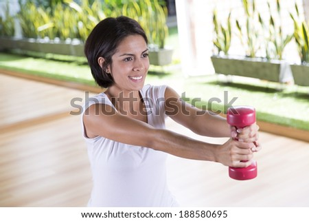 Portrait of Attractive Woman Exercising With Dumbbells - stock photo