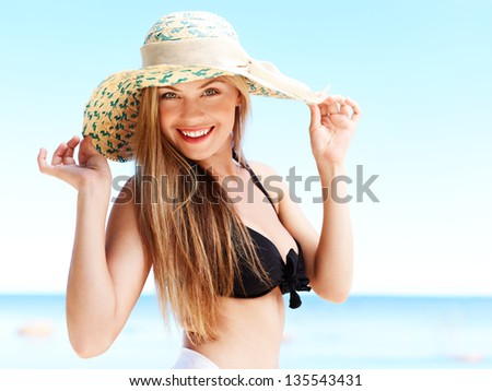 Portrait of attractive woman in a straw hat. Medium format image.