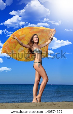 Portrait of attractive woman in bikini on the beach holding a sarong - stock photo