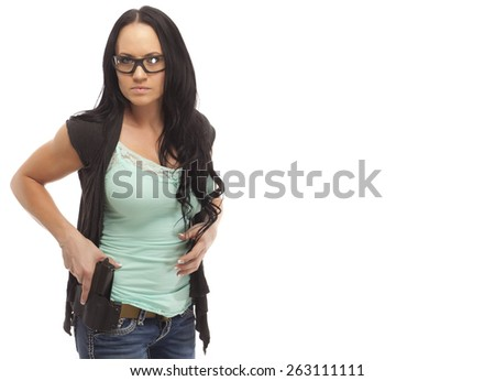 Portrait of attractive woman in protective eye wear holding handgun in holster - stock photo