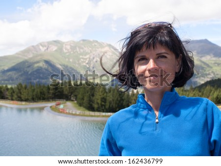 Portrait of attractive woman in the mountains near lake - stock photo
