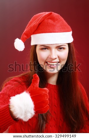 Portrait of attractive woman isolated on red, studio shot in christmas hat