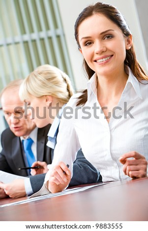 Portrait of attractive woman sitting at the table with business people near by