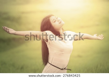 Portrait of attractive woman with casual clothes enjoying freedom at field, shot with an instagram filter - stock photo