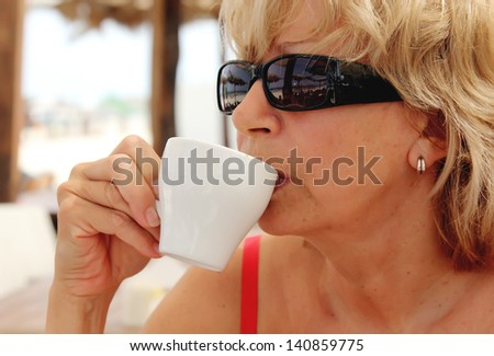 Portrait of attractive woman with cup of hot drink (coffee or tea) at the beach - stock photo