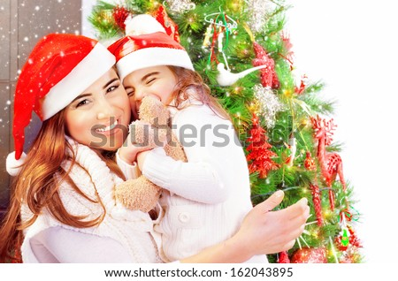 Portrait of attractive woman with daughter celebrate New Year at home, wearing red Santa hats, girl receive as gift soft toy of bear - stock photo