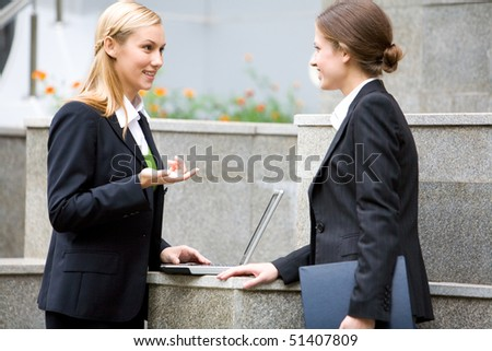 Portrait of attractive women discussing about work near building - stock photo