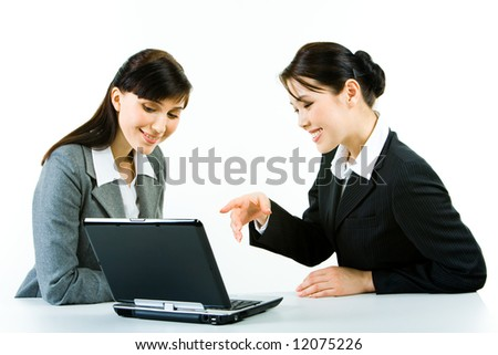 Portrait of attractive women sitting at the table and looking at the laptop monitor - stock photo