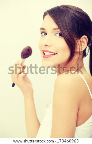 Portrait of attractive young adult woman applying blusher in her bathroom - stock photo