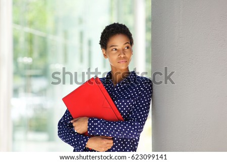 Portrait of attractive young african american business woman standing outside