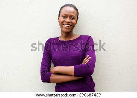 Portrait of attractive young african american woman standing with arms crossed against white wall - stock photo