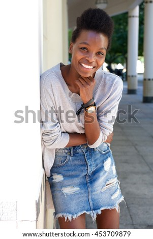 Portrait of attractive young african woman standing outdoors and smiling
