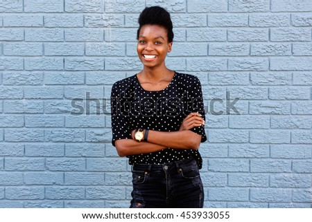 Portrait of attractive young african woman standing with her arms crossed against gray brick wall  - stock photo