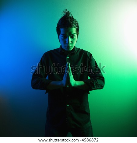 Portrait of attractive young Asian Filipino man standing holding hands in prayer position. - stock photo