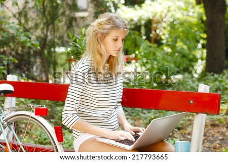 Portrait of attractive young blogger working on laptop while sitting at park. - stock photo