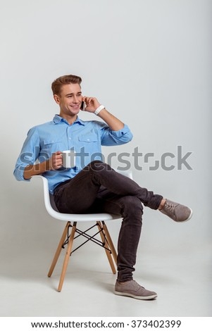 Portrait of attractive young blond businessman in blue shirt smiling, looking away, holding a cup and talking on the phone, sitting against gray background