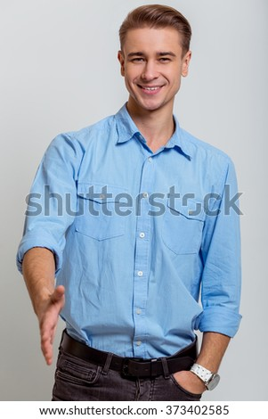 Portrait of attractive young blond businessman in blue shirt smiling, looking in camera and stretching his hand, standing against gray background - stock photo