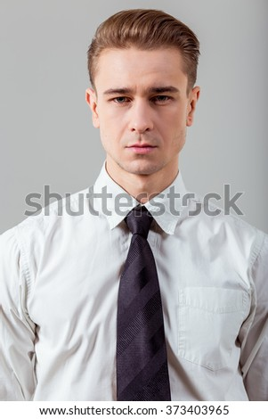 Portrait of attractive young blond businessman in white classical shirt and dark tie, standing against gray background and looking in camera - stock photo