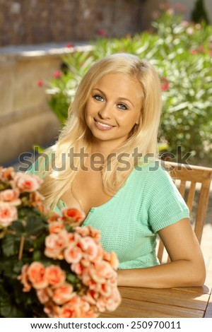 Portrait of attractive young blonde busty caucasian lady sitting in chair outdoors in a summer garden with flowers. Smiling. - stock photo