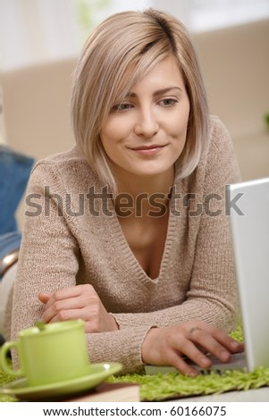 Portrait of attractive young blonde woman lying on floor at home looking at laptop, smiling.? - stock photo