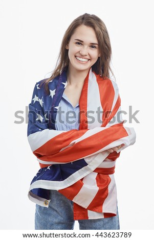 Portrait of attractive young brunette girl wrapped in National Flag celebrating Independence Day on 4th of July in United States of America.Cute model with toothy smile on isolated background - stock photo