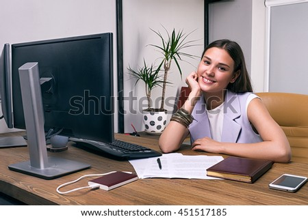 Portrait of attractive young brunette sitting at desk and smiling at camera - stock photo