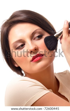 Portrait of attractive young brunette woman applying blusher - stock photo