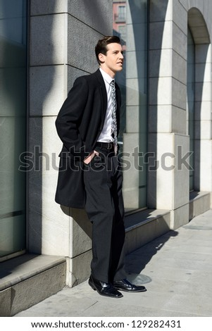 Portrait of attractive young businessman in urban background
