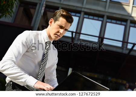 Portrait of attractive young businessman typing in a laptop computer in urban background