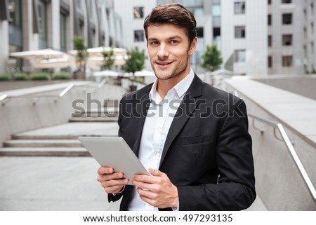 Portrait of attractive young businessman using tablet near business center