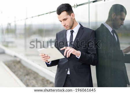 Portrait of attractive young businessman with a tablet computer in an office building