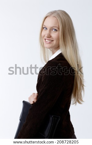 Portrait of attractive young businesswoman in black holding briefcase smiling happy. - stock photo