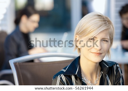 Portrait of attractive young businesswoman sitting in chair, smiling. - stock photo