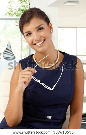 Portrait of attractive young caucasian businesswoman in formal dress, glasses in hand, looking at camera, smiling. - stock photo