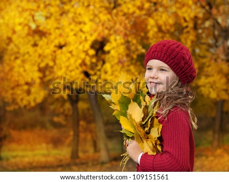portrait of attractive young caucasian girl in warm colorful clothing  on yellow leaves outdoors smiling looking up - stock photo