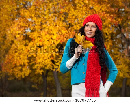 portrait of attractive young caucasian woman in warm colorful clothing  on yellow leaves outdoors smiling looking at camera